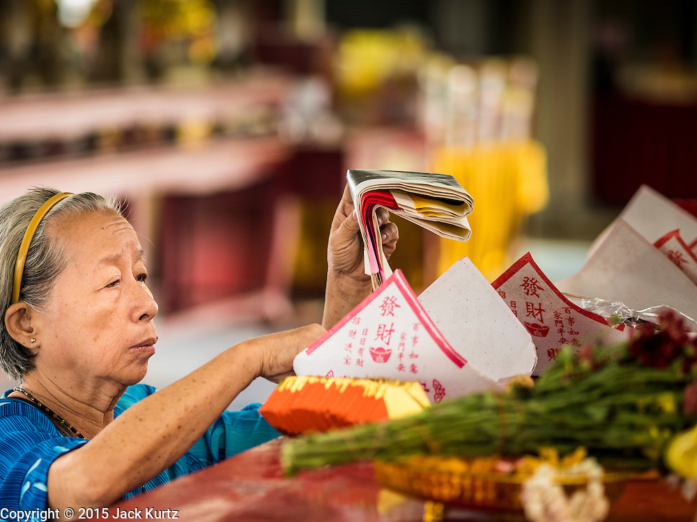 10 SEPTEMBER 2015 - BANGKOK, THAILAND:  A woman prays in Wat Kalayanamit. The controversial abbot of the temple has ordered the destruction of 54 homes in front of the temple, a historic Buddhist temple on the Chao Phraya River in the Thonburi section of Bangkok. Government officials, protected by police, seized the house of Chaiyasit Kittiwanitchapant, a Kanlayanamit community leader, who has led protests against the temple's abbot for trying to evict community members whose houses are located around the temple. Work crews went into Chaiyasit's home and took it apart piece by piece. The abbot of the temple said he was evicting the residents, who have lived on the temple grounds for generations, because their homes are unsafe and because he wants to improve the temple grounds. The evictions are a part of a Bangkok trend, especially along the Chao Phraya River and BTS light rail lines, of low income people being evicted from their long time homes to make way for urban renewal.    PHOTO BY JACK KURTZ