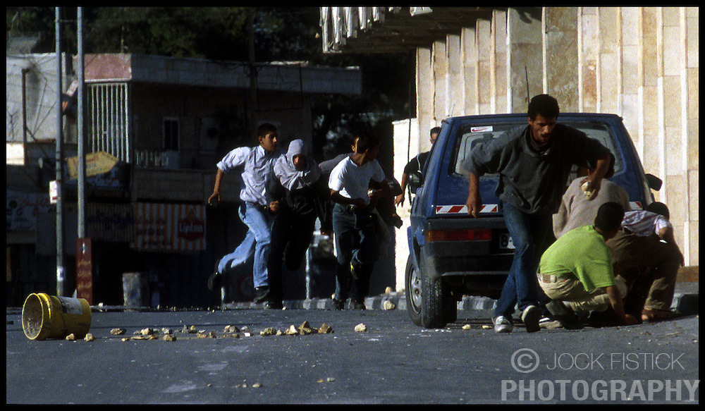 Palestinian youths run for cover during a clash with Israeli soldiers near Rachel's Tomb in the West-bank city of Bethlehem. (Photo © Jock Fistick)