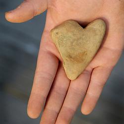 Marie Ammar, 9, holds a heart-shaped stone she found on the beach behind their home...Photo by Susana Raab