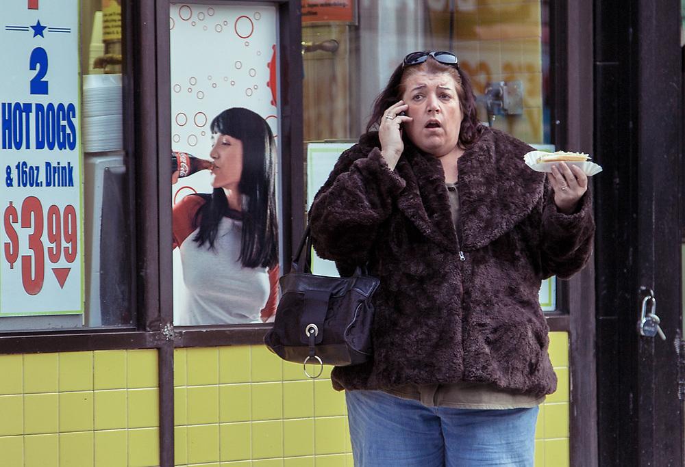 Woman eating hotdog in front of the old Papaya dog 42nd & 9th Av. NYC 2012