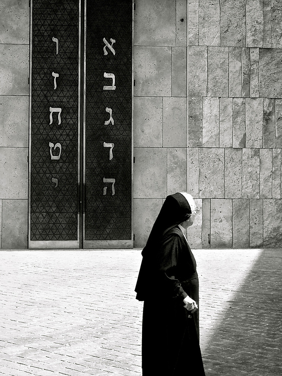 In old Munich, not far from the Marienplatz is a world famous synagogue.  Right place, right time to catch this poignant image of a German nun passing its doors.