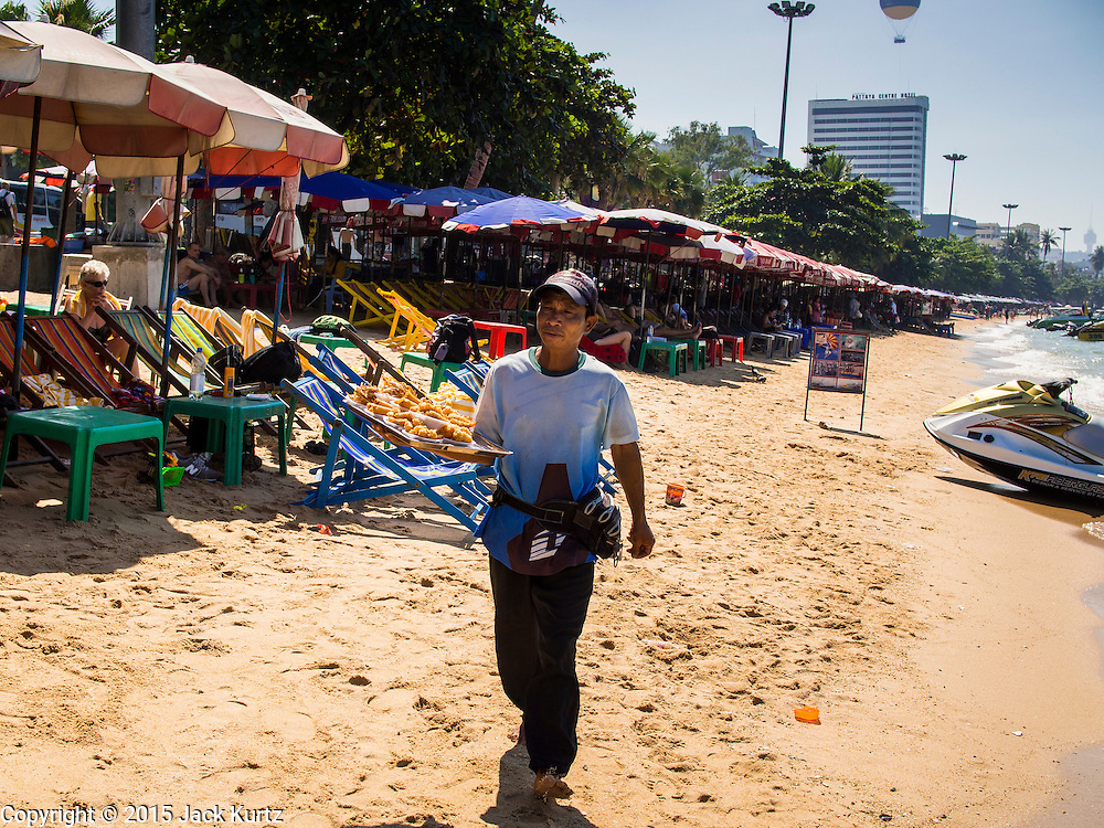 06 JANUARY 2015 - PATTAYA, CHONBURI, THAILAND: A food vendor walks past tourists sleeping under rented umbrellas on rented chaise lounges on Pattaya beach. The Thai government has announced plans to clean up Pattaya beach, one of the most famous beaches in Thailand. Pattaya is about 2.5 hours from Bangkok. They plan to reduce the number of umbrella and chaise lounge vendors on the beach and regulate the personal watercraft and parasailing vendors on the beach. The government has already cleaned up beaches on Phuket island and Hua Hin.    PHOTO BY JACK KURTZ