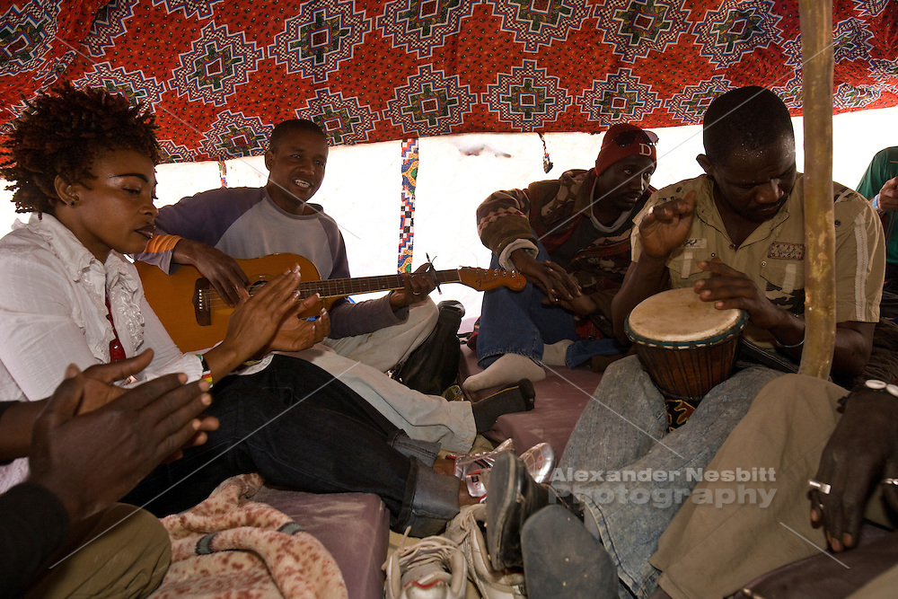 Essakane, Mali, West Africa, 2009 -  At the Festival au Desert music festival Veaux Farka  son of Ali Farka Toure.  jams  informally with friends and band members under a small  tent  with just a handful of spectators squeezed in along the sides.