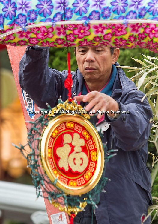 A man decorates at Hsi Lai Temple on February 8, 2013 in Los Angeles, California, ahead of the Lunar New Year. Preparations continue for the Lunar New Year which will celebrate the Year of the Snake on February 10. (Photo by Ringo Chiu/PHOTOFORMULA.com).