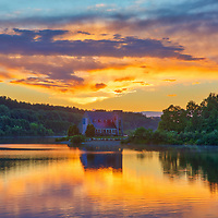 Abandoned Old Stone Church in West Boylston, MA on a beautiful night at sunset. This National Historic Site is located on the banks of the Wachusett Reservoir. On my recent visit, a waited out a fast moving weather system with downpours and rainbows before Mother nAture turned on a magic switch. The sunset turned into a sky fire where its light painted this Central Massachusetts historic landmark and cloudscape in stunningly beautiful hues that reflected into the calm waterscpe of the Wachusett Reservoir.<br />