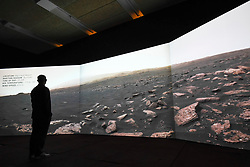 "© Licensed to London News Pictures. 17/10/2019. LONDON, UK. A staff member views a video projection showing the view on Mars from the Curiosity rover. Preview of ""Moving to Mars"" at the Design Museum. The exhibition explores how sending humans to Mars is a frontier for science as well as design and features over 200 exhibits from NASA, the European Space Agency together with new commissions.  The show is open 18 October to 23 February 2020.  Photo credit: Stephen Chung/LNP"