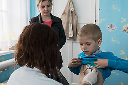 Oksana, 32, has brought Sergey, 8, to be examined by Dr Galina Piskunova at the Zorinks health centre where MSF have set up a mobile clinic.