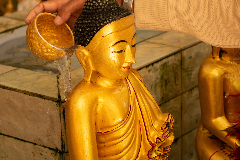 Bathing a  Buddha statue for a blessing, A religious ritual. Pouring water onto Buddha statue is a gesture of worship to the lord Buddha, and would bring them prosperity and happiness