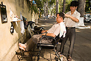 09 MARCH 2006 - HO CHI MINH CITY, VIETNAM: A barber works on a street in Ho Chi Minh City (formerly Saigon) Vietnam. With an unofficial population of nearly 10 million (the official population is 6 million) business is done anywhere a businessperson can find space to do it, including the sidewalk. Photo by Jack Kurtz / ZUMA Press