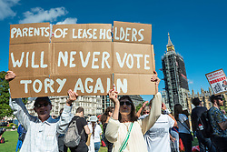 © Licensed to London News Pictures. 16/09/2021. LONDON, UK.  A  couple hold up a sign at a Leaseholders Together Rally in Parliament Square.  Organised by End Our Cladding Scandal campaign together with the National Leasehold Campaign (NLC) and charity Leasehold Knowledge Partnership, people were protested at restrictions to leasehold rights as well as the current cladding crisis.  Photo credit: Stephen Chung/LNP