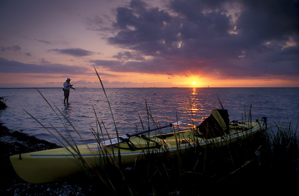 Stock photo of a fisherman with his yellow kayak standing in the shallow water of the bay flyfishing at sunset on the Texas Gulf coast.