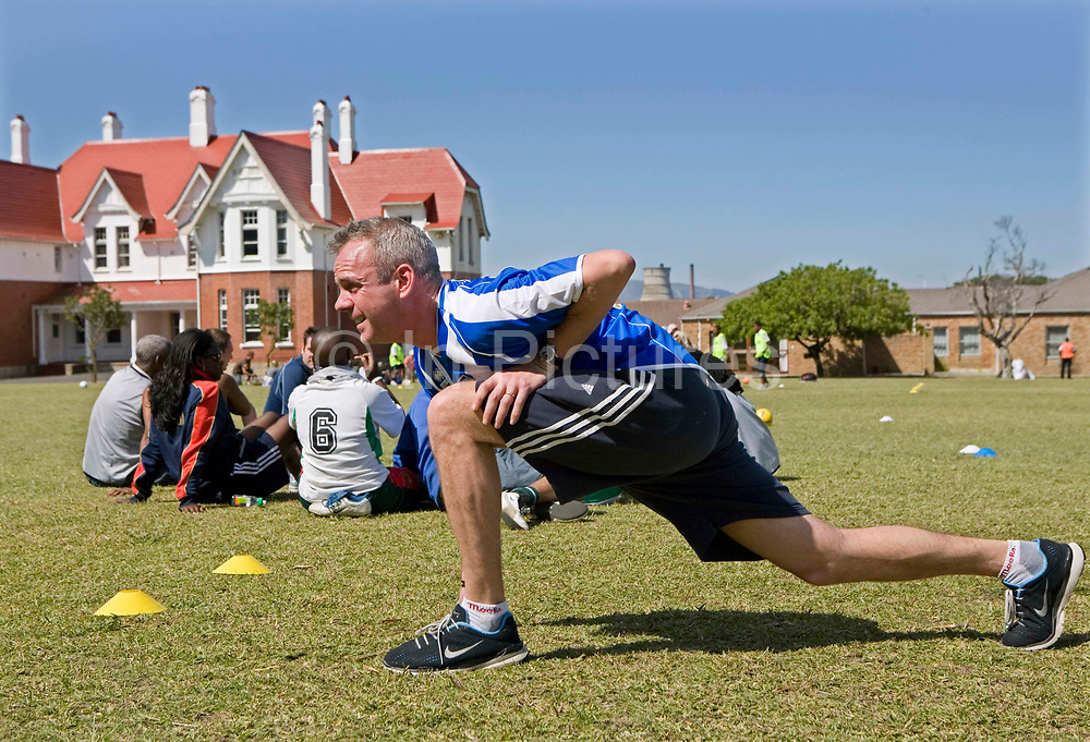 """Norman Cook warms up in football attire in South Africa where he is helping the charity, Coaching for Hope. In 2006 Norman Cook aka """"Fatboy Slim"""" agreed to be the patron of Coaching for Hope.  His record company """"Skint"""" had long been the sponsors of Brighton and Hove Albion, one of the football clubs that has supported Coaching for Hope from the start. The charity is an innovative programme, which uses football to create better futures for young people in West and Southern Africa."""