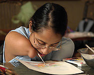 Directv Magazine -- Minda Cox works on a painting during an afternoon at Camp Barnabas.