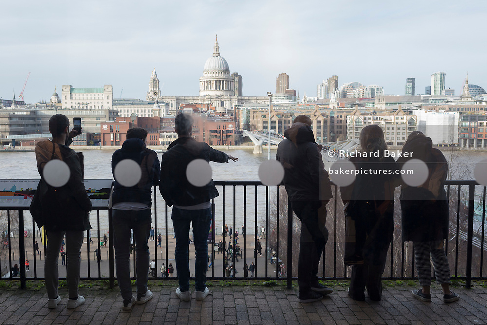 Spectators look out over the Thames to St. Paul's Cathedral from the balcony on the third floor of Tate Modern, on 10th March 2019, in London, England.