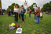 """Protestors hold placards """"NO MORE WARS"""" during a protest """"for Afghanistan"""" outside Westminster Palace, Houses of Parliament in central London on Wednesday, Aug 18, 2021. British Prime Minister Boris Johnson is expected to address the Parliament later today. (VX Photo/ Vudi Xhymshiti)"""