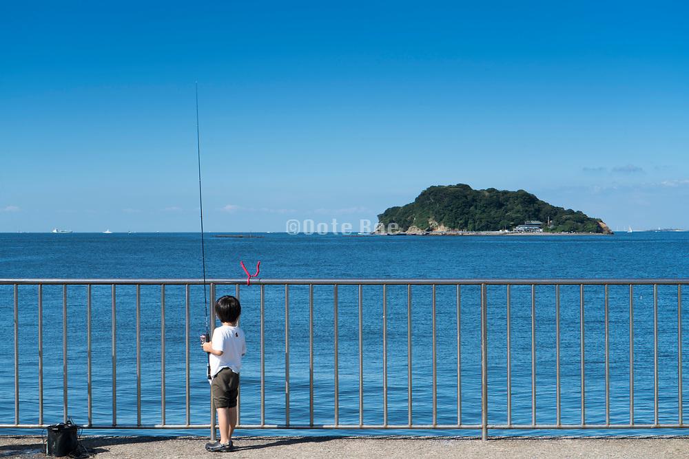 a little child fishing at Umikaze park, Yokosuka with Tokyo Bay and Sarushima Island