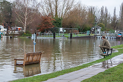 © Licensed to London News Pictures. 04/02/2021. London, UK. An angler takes advantage of the rising Thames in Chertsey, Surrey. Flooded streets and property in Laleham, Surrey. Flooding in parts of  Laleham and Chertsey in Surrey as rising flood water continues to rise around riverside properties in the area. The Uk is set to be battered by heavy rainfall, flooding and snow storms this weekend as the Met Office issue warnings that snow could hit most of the country in the coming days. Photo credit: Alex Lentati/LNP