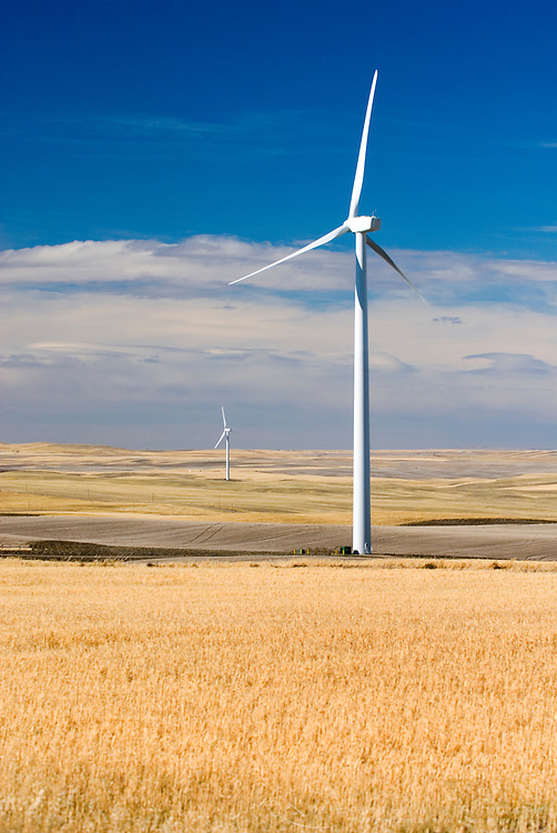 Wind turbines stand amidst the plains of eastern Montana near the Rocky Mountain front ranges of Glacier National Park USA