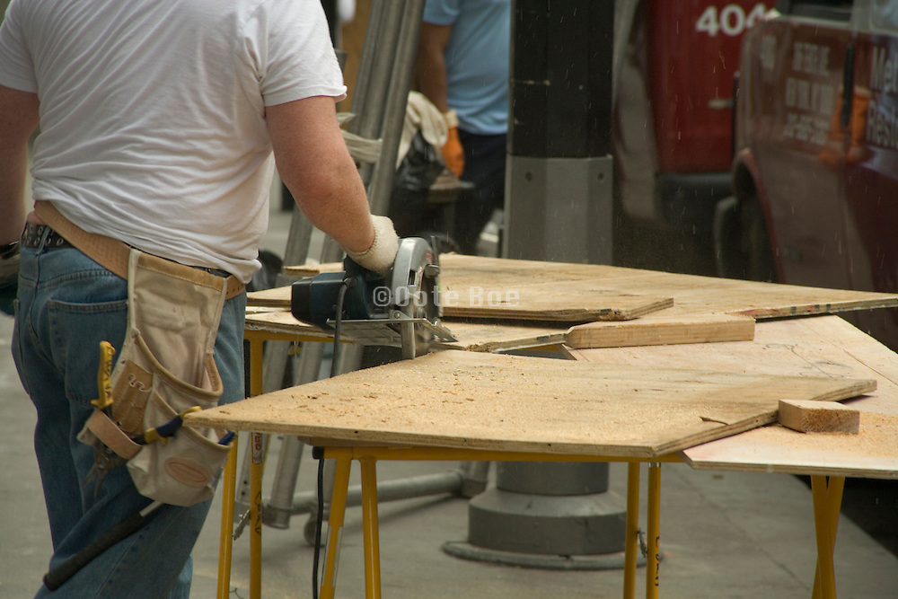 construction worker working with a circular saw cutting wood