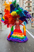 A marcher on 5th Avenue wearing an elaborate rainbow costume.
