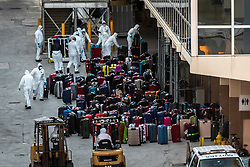 Workers dressed in protective clothing manage luggage unloaded from the Holland America cruise ship Zaandam, at Port Everglades, in Fort Lauderdale on Thursday, April 2, 2020. Holland America confirmed that a number of passengers are infected with the coronavirus.