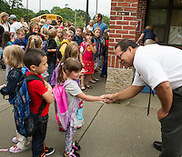 Kindergartener Emmah Durette is a little shy as she says hello to Elm Street School Principal Mr. Kevin Michaud on their first day of school Tuesday morning.  (Karen Bobotas/for the Laconia Daily Sun)