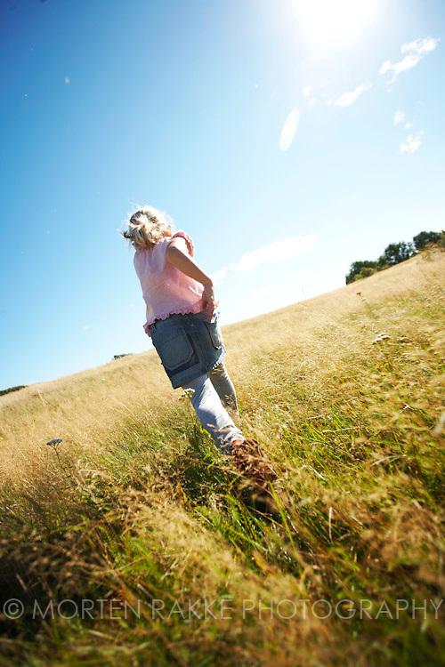 Girl running in grassland, rear view