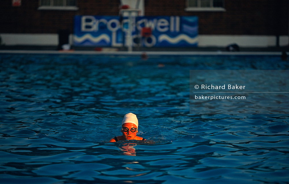 Early morning regular swimmer swims solitary lengths at Brockwell (Brixton) Lido before crowds arrive