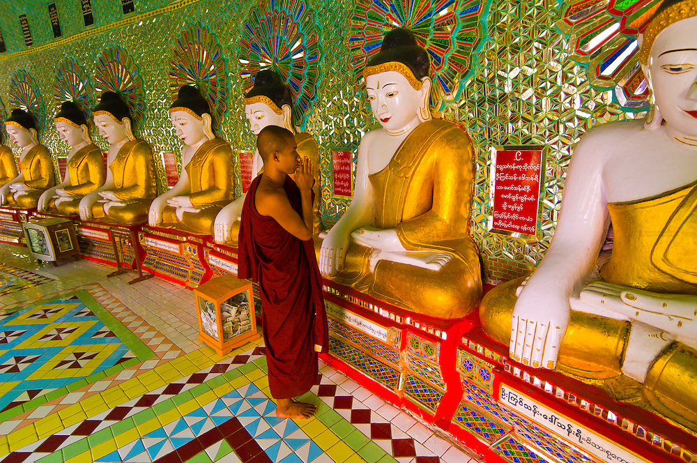 Monk praying in front of row of Buddhas, Umin Thounzeh caves, Sagaing, Myanmar (Burma)