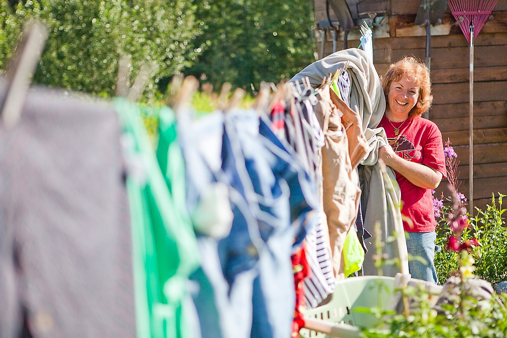 Kayane James stands by a colorful clothesline at her home and bed and breakfast (Alaska Halfway House B&B) in Chokosna, 27 miles up the McCarthy Road into Wrangell-St. Elias National Park, Alaska.