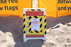 © Licensed to London News Pictures. 29/05/2020. Padstow, UK. A sign displays safety information as RNLI Lifeguards resume service on Constantine beach on the north coast of Cornwall this morning, as one of a select few beaches. Up until today, the RNLI have not been providing a lifeguard service in Cornwall, due to Coronavirus (COVID-19). The weather in the south-west is forecast to be warm over the weekend, with highs of 23 degrees Celsius. Photo credit : Tom Nicholson/LNP