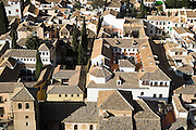 Top view of the historic whitewashed buildings and tile roofs below La Alhambra in Granada, Andalusia, Spain.