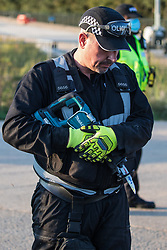 West Hyde, UK. 14th September, 2020. An officer from a Hertfordshire Police cutting team prepares to remove HS2 Rebellion activists using lock-on arm tubes to block a gate to the South Portal site for the HS2 high-speed rail link. Anti-HS2 activists blocked two gates to the same works site for the controversial £106bn rail link, one remaining closed for over six hours and another for over nineteen hours.