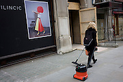 Woman cleaner pulling a vacuum hover behind her, walks past a fashion poster in central London.