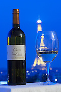Cuvee des Conti Chateau Tour des Gendres, Bergerac, against a background of a view over Paris with dark blue sky and illuminated Eiffel Tower and a glass of wine Bergerac Dordogne France