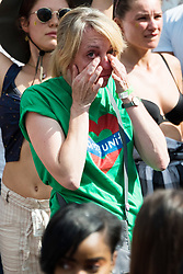 © Licensed to London News Pictures. 27/08/2017. London, UK. A woman wipes tears at the Notting Hill Festival before a minutes silence as a mark of respect for the victims of the Grenfell Tower fire disaster. It is second largest street festival in the world after the Rio Carnival in Brazil, attracting over 1 million people. Photo credit: Ray Tang/LNP