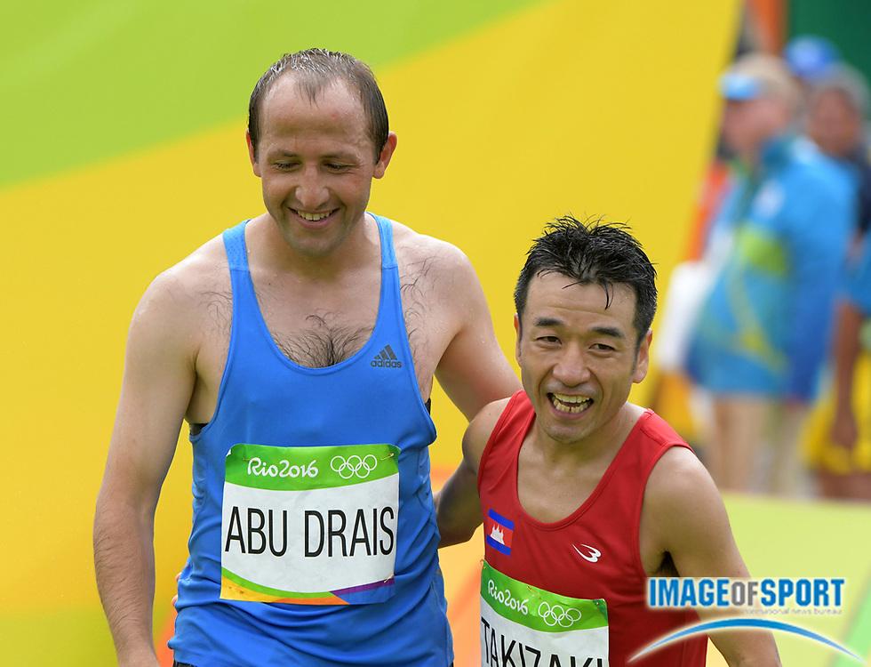 Aug 21, 2016; Rio de Janeiro, Brazil; Methgal Marouf Abu Drais (JOR) and Kuniaki Takizaki (CAM) embrace after the marathon during the Rio 2016 Summer Olympic Games at Sambodromo.