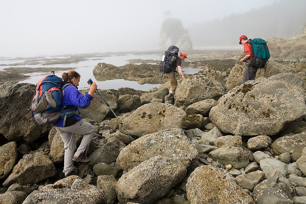 Backpackers navigate the rugged coastline and large boulders at Norwegian Memorial, North Coast, Olympic National Park, Washington.