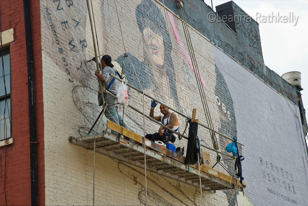 Artists paint a billboard for Barney's New York along the side of a building in downtown Manhattan.