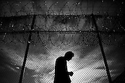 An inmate walks by the barbed wire fence back to his cell after having lunch.  The Bristol County Jail & House of Correction located on Ash Street in New Bedford, Massachusetts was started in 1829, and is the oldest running jail in the United States.   The Ash street jail, as it is known, has been a controversial facility since it opened.  It is believed to be the site of the last pubic hanging in Massachusetts sometime in the 1890's.  Two big riots broke out in the 90's (1993, 1998) and since then the facility has been modified to alleviate some of the crowded conditions that resulted in the riots.