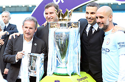 Manchester City director of football Txiki Begiristain (left), chairman Khaldoon Al Mubarak (second right) and manager Pep Guardiola (right) celebrate with the Premier League trophy and League Cup after the Premier League match at the Etihad Stadium, Manchester.