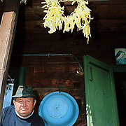 A Romanian man sits outside his wooden home with a string of beans hanging above his head, Botiza, Maramures, Romania