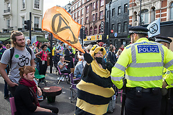 London, UK. 23rd August, 2021. Metropolitan Police officers ask environmental activists from Extinction Rebellion to move out of a road in the Covent Garden area during the first day of Impossible Rebellion protests. Extinction Rebellion are calling on the UK government to cease all new fossil fuel investment with immediate effect. Credit: Mark Kerrison/Alamy Live News