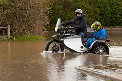 © Licensed to London News Pictures. 18/02/2020. Upton-upon-Severn, Worcestershire, UK. A man and child ride through a flooded car park on a motor bike and sidecar at Upton-upon-Severn in Worcestershire, UK. Though river levels have dropped fractionally, a severe flood warning is still in force at Upton-upon-Severn, in Worcestershire, UK. Photo credit: Graham M. Lawrence/LNP