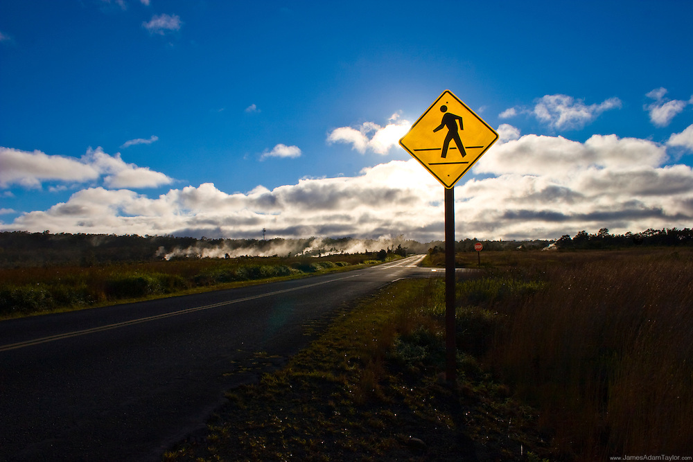 a Pedestrian crossing sign warns motorists of road crossing tourists in Volcanoes National park, Hawaii .