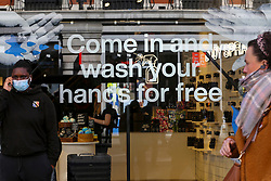 "© Licensed to London News Pictures. 11/03/2020. London, UK. A shopper wearing a surgical face mask stands next to a ""COME IN AND WASH YOUR HANDS FOR FREE' window display on Oxford Street. Chancellor RISHI SUNAK has unveiled a £30bn package to help the economy get through the coronavirus outbreak in the UK. Photo credit: Dinendra Haria/LNP"