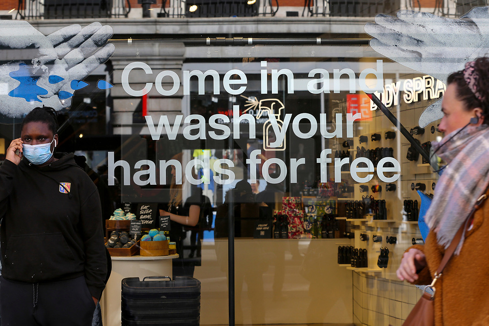 """© Licensed to London News Pictures. 11/03/2020. London, UK. A shopper wearing a surgical face mask stands next to a """"COME IN AND WASH YOUR HANDS FOR FREE' window display on Oxford Street. Chancellor RISHI SUNAK has unveiled a £30bn package to help the economy get through the coronavirus outbreak in the UK. Photo credit: Dinendra Haria/LNP"""