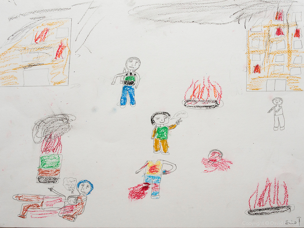 """""""There is a hospital in the upper right, a mother crying for her son in the lower left. The child in the bottom center was eating a candy bar when a bomb blew his head off. The girl who drew this witnessed it. He remained standing for a few moments with the candy bar after it happened."""" Drawing by Syrian girl, age 13. (Topic for this session: dealing with loss.)"""