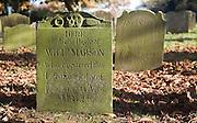 Gravestones in rural churchyard, Reydon, Suffolk, England with brown fallen autumn leaves