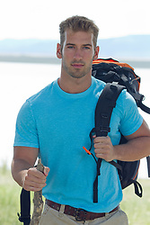 PhotoLibrary-RJ sexy man with a backpack outdoors by a lake